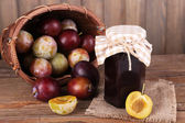 Tasty plum jam in jar and plums on wooden table on wooden background — Stock fotografie