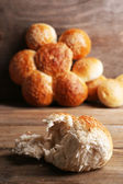 Tasty buns with sesame on color wooden background — Stock fotografie