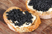Slices of bread with butter and black caviar on wooden background — Stockfoto