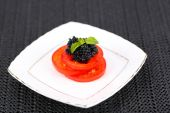 Slices of tomato with black caviar on plate on dark fabric background — Stockfoto