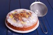 Delicious cake and sieve with powdered sugar on wooden table — Stock Photo