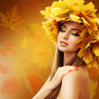 Beautiful young woman with yellow autumn wreath on bright background — Stock Photo #52390953