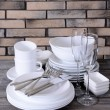 Set of white dishes on table on brick-wall background — Stock Photo #52524009