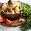 Young boiled potatoes in pan with vegetables on wooden table, close up — Stock Photo #52524107