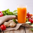 Glass of fresh carrot juice and vegetables on sacking napkin on wooden table — Stock Photo #52525061