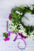 Wildflower wreath on grey wooden background — Stock Photo