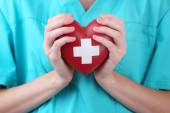 Red heart with cross sign in doctor hand, close-up, isolated on white — Stock Photo