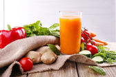 Glass of fresh carrot juice and vegetables on sacking napkin on wooden table — Stock Photo