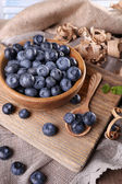 Wooden bowl of blueberries on cutting board on sacking napkin — Stock Photo