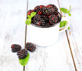Metal mug of blackberries on wooden background — Stock Photo