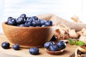 Wooden bowl of blueberries on cutting board on sacking napkin on light background — Stock Photo
