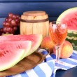 Composition of ripe watermelon, fruits, pink wine in glass and wooden barrel on color wooden background — Stock Photo #52537655