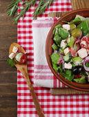 Kom van griekse salade geserveerd op snijden bestuur servet op houten tafel op donkere achtergrond — Stockfoto