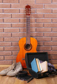 Guitar, trainers and clothes on brick wall background — Foto Stock