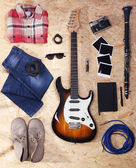 Musical equipment, clothes and footwear on wooden background — Stock Photo
