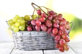 Bunches of ripe grape in wicker basket on wooden table on natural background — Stock Photo