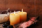 Spa stones with candles and sea salt on wooden background — Stock fotografie
