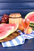 Composition of ripe watermelon, fruits, pink wine in glass and wooden barrel on color wooden background — Zdjęcie stockowe