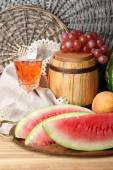 Composition of ripe watermelon, fruits, pink wine in glass and wooden barrel on  color wooden table, on bricks background — Fotografia Stock