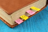 Book with bookmarks on color wooden background — Stock Photo