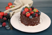 Tasty chocolate cake with different berries, on wooden table — Stock Photo