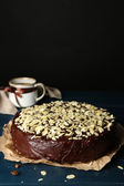 Tasty chocolate cake with almond, on wooden table, on dark background — Stockfoto
