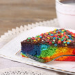 Delicious rainbow cake on plate and cup with hot drink, on wooden background — Stock Photo #52647069