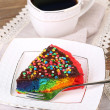 Delicious rainbow cake on plate and cup with hot drink, on wooden background — Stock Photo #52647073