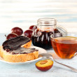 Bread with plum jam and tea on wooden table — Stock Photo #52648991