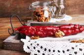 Tasty oriental sweets (churchkhela) and fresh nuts, on wooden background — Foto de Stock