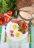 Scrambled eggs with bacon and vegetables served on plate on fabric background — Stock Photo