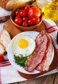 Scrambled eggs with bacon and vegetables served on plate on napkin — Stock Photo