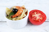 Fresh prawns with coloured macaroni and olives in a round bowl on wooden background — Foto Stock
