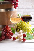 Wine with grapes on table on brick wall background — Stock Photo