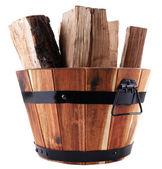 Round wooden basket full of firewood isolated on white — Stock Photo