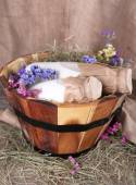 Big round basket with dried grass, milk and fresh eggs on sacking background — Stock Photo