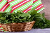 Fresh sorrel in round wicker basket on wooden background — Stock Photo