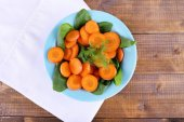 Slices of carrot, sorrel and dill in blue round bowl on napkin on wooden background — Stockfoto