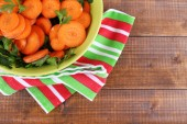 Slices of carrot, sorrel and parsley in green round bowl on napkin on wooden background — Stock Photo
