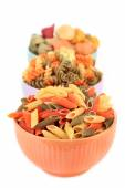 Assortment of colorful pasta in color bowls isolated on white — Stock Photo