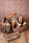 Box of firewood and axe on floor on brick background — Stock Photo