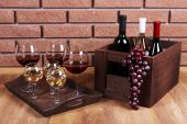 Bottles and glasses of wine and ripe grapes on table on brick wall background — Stock Photo