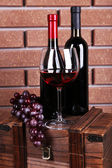 Bottle and glass of wine and ripe grape on box on brick wall background — Foto de Stock