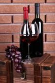 Bottle and glass of wine and ripe grape on box on brick wall background — ストック写真