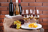 Bottles and glasses of wine, cheese and ripe grapes on table on brick wall background — Foto de Stock
