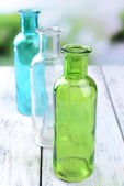 Empty glass bottles on table on bright background — Stock Photo