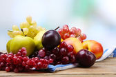 Assortment of juicy fruits on napkin, on table, on bright background — Stock Photo