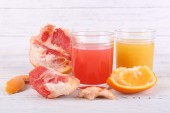 Different sliced citrus fruits and glasses of juice on wooden table — Stock Photo