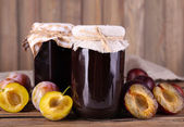 Tasty plum jam in jars and plums on wooden table on wooden background — Stock Photo