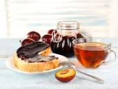 Bread with plum jam and tea on wooden table — Stock Photo